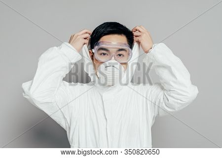 Asian Epidemiologist In Hazmat Suit And Respirator Mask Putting Hood On While Looking At Camera On G