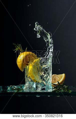 Cocktail Gin-tonic With Lemon And Rosemary. Carbonated Drink With Ice Pieces On A Glass Table. Black