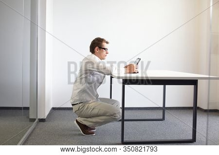 man squatting at the desk, working with tablet - changing position