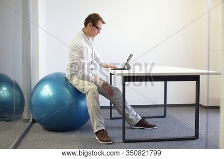 Man on stability ball working with tablet at desk in the office