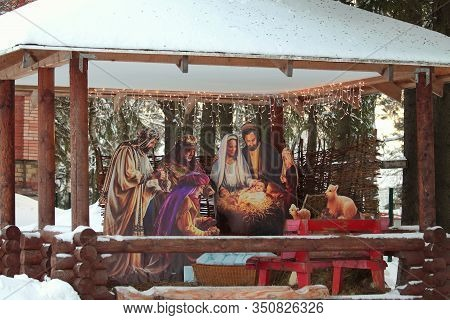Colorful Christmas Nativity Scene Decorated With A Luminous Garland, A Scene Of The Birth Of Jesus.