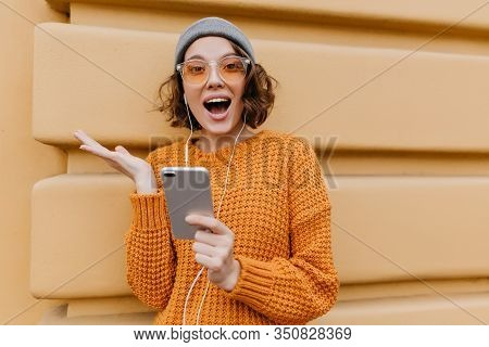 Active Girl In Trendy Cozy Attire Posing With Happy Face Expression, Holding Smartphone. Excited You