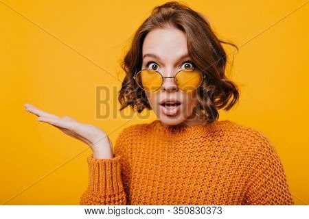 Close-up Portrait Of Shocked Young Lady With Big Brown Eyes And Mouth Open. Curly Woman In Yellow Kn