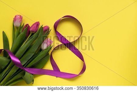 Beautiful Spring Tulips And Ribbon Eight Shaped On Yellow Background. Concept Of Valentines Day, Wom