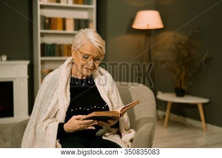 Woman Of Retirement Age Rests In Armchair Reading Old Book. Charming Gray-haired Lady Threw White Pl
