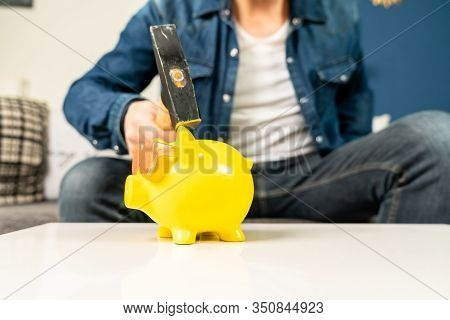A Man Smashes His Piggy Bank On A Table In His Living Room