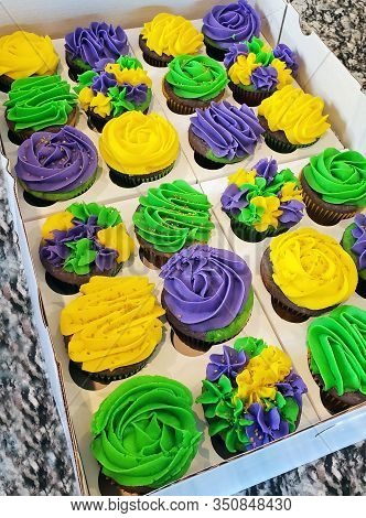 Two Dozen Colorful, Purple, Lime Green And Golden Yellow Mardi Gras, Chocolate, Cupcakes In A Bakery
