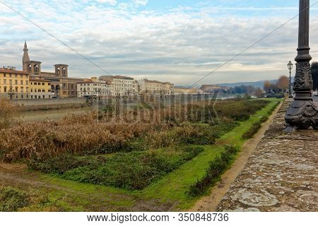 View Of Florence Firenze Italy Italia And Arno River With Buildings Grass And Flowers On The Shore
