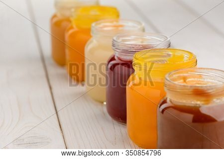 Close Up On Jars Of Baby Food On Wooden Table