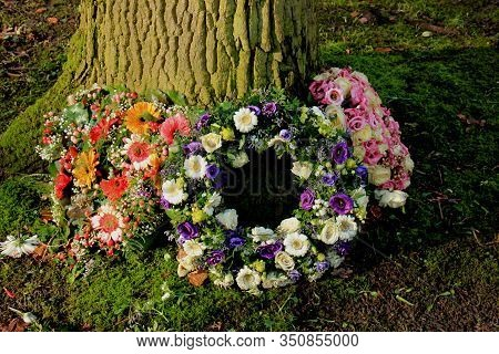 Sympathy Wreath Or Funeral Flowers Near A Tree