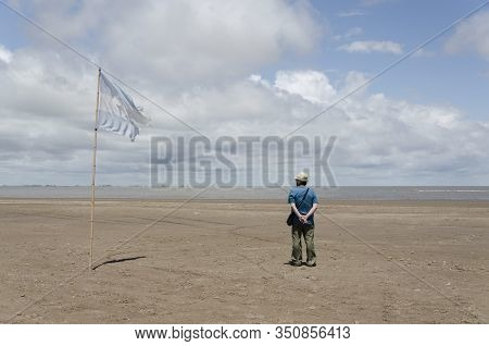 Punta Rasa, Buenos Aires / Argentina: Dec 31, 2015: Man Seen From Behind Watching The Sea, Next To A