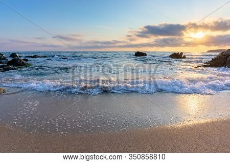 Sunrise On The Beach. Beautiful Summer Scenery. Rocks On The Sand. Calm Waves On The Water. Clouds O
