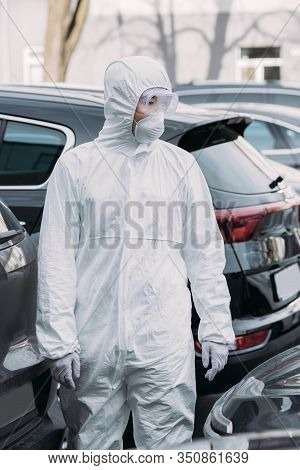 Asian Epidemiologist In Hazmat Suit And Respirator Mask Inspecting Cars On Parking Lot