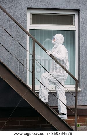 Asian Epidemiologist In Hazmat Suit And Respirator Mask Walking Upstairs Outside Building