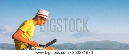 Young Travel Blogger With Laptop In Mountains. Freelancer With Laptop In Mountains. 4g, 5g Connectio