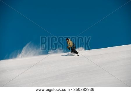 Man Freerider Glides Down On The Mountain Side