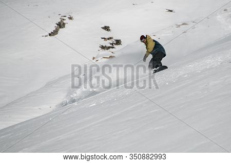 Male Freerider Glides Down The Snowy Mountain Slope