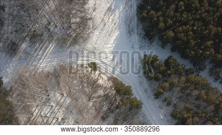 Aerial View Of The Road Passing Through The Winter Forest Covered With Ice. The Road Through The Con