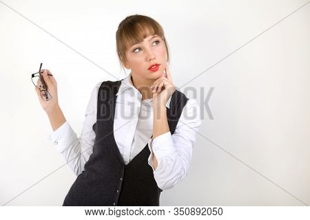 Intrigued Young Beautiful Woman Manager Or Secretary In Formal Clothes On A White Background Looks A