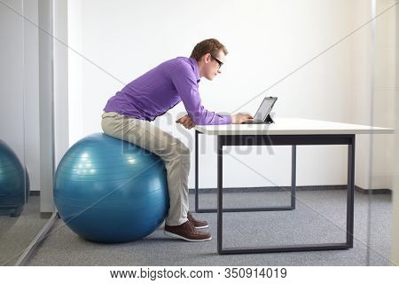 Man on stability ball working with tablet at desk in the office - changing position