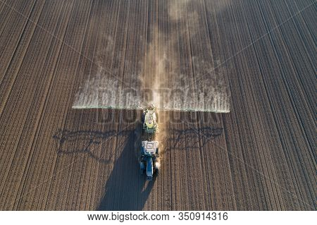 Aerial Image Of Tractor Spraying Agricultural Field In Springtime At Sunset