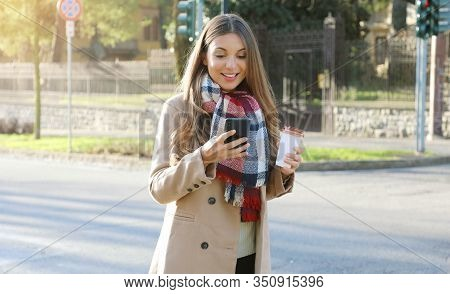 Portrait Of Young Business Woman Wearing Coat And Scarf Walking In City Street Messaging With Phone