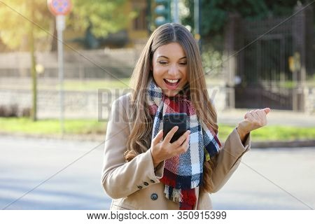 Successful Business Woman Exults Reading Good News On Mobile Phone. Beautiful Young Business Woman E