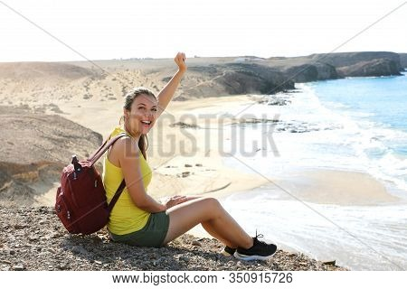 Portrait Of Young Female Hiker Reaches Top Of Mountain And Celebrates With Amazing Landscape On The