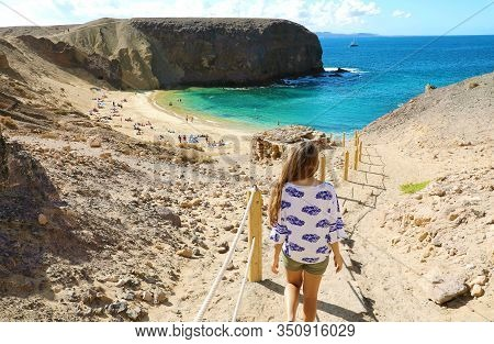 Holidays In Lanzarote. Back View Of Young Beautiful Woman Goes Down To The Amazing Beach Playa Papag