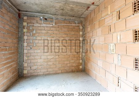 Unfinished Room Interior Of Building Under Construction. Brick Red Walls. New Home.