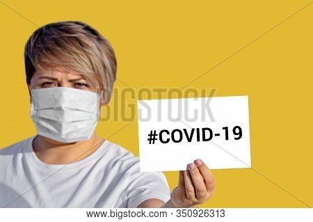 Woman In Face Mask Hold Blank With Inscription Covid-19. World Health Organization Who Introduced Ne