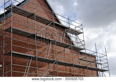 Big Scaffolding On The Facade Of A House To Renovate And Insulate The Wall, The Wall Is Built In Red
