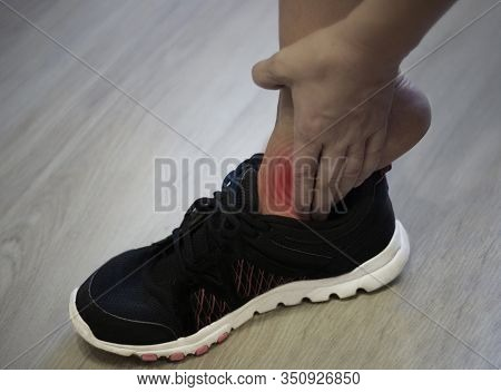 Young Woman Massaging Her Painful Foot From Exercising And Running Sport And Excercise Concept. Woma