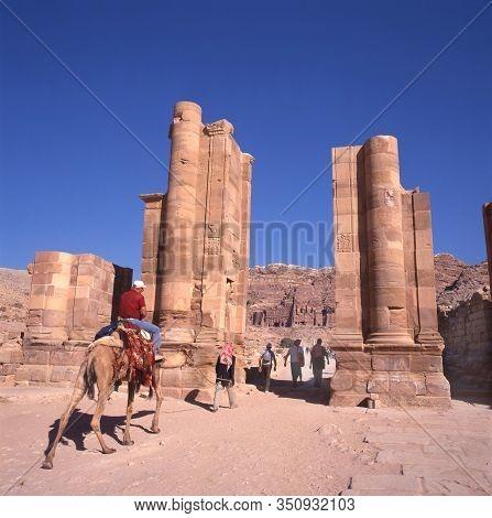 Petra,jordan-august 14,2001:tourists And Guide On Dromedaries At Temenos Gate, Center Of Petra, Anci