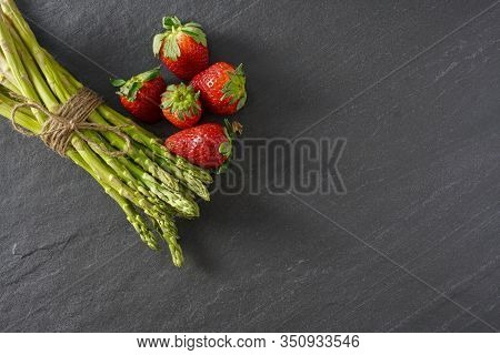 Flay Lay Of A Bunch Of A Spring Harvest Of Asparagus And Strawberries On A Gray Slate Counter