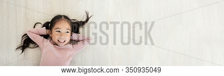 Smiling Asian Child Girl In Pink Sweater Looking Up And Sleep On Wooden Floor On Holidays. Having Fu