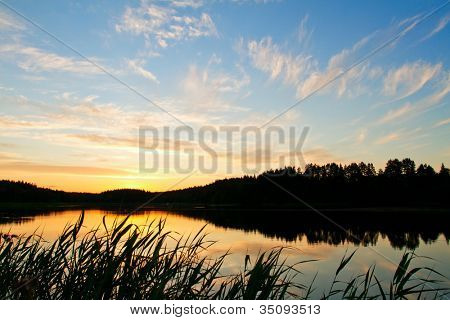 Beautiful sunset over the forest lake
