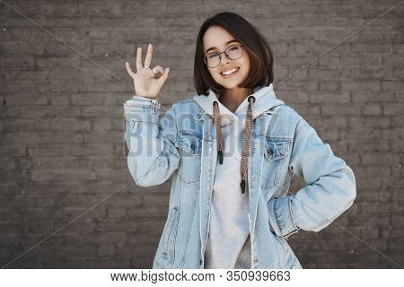 No Problem. Carefree Positive Young Caucasian Female Student With Short Hair, Wearing Glasses And De