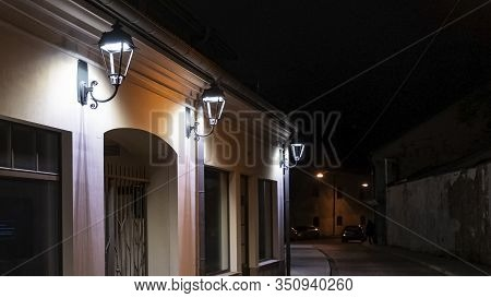 Old Street At Night. Street Llamps On The Wall Building.