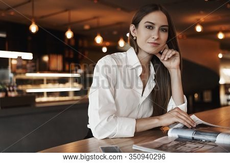 Elegant Young Businesswoman Reading Magazine While Sitting In Cafe, Leaning Desk, Wearing White Blou