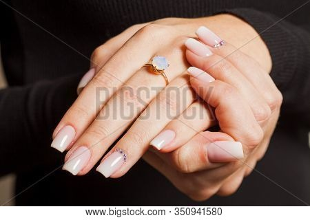 Woman Showing The Ring With Stone. Woman Is Engaged. Beauty Hands With Tender Manicure, Close-up.