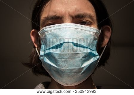 Man Wearing A Surgical Face Mask Covering The Lower Half Of His Face.medical And Healthcare Concept.