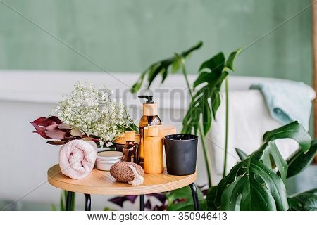 Composition Set Of Spa Treatment On Wooden Table In Modern Eco Natural Interior Of Bathroom With Gre