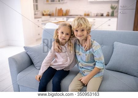 Two Blod Kids Sitting Next To Each Other And Hugging