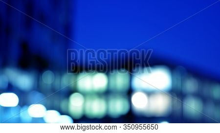 Blurred Night Architecture - Building With Glass Facade. Modern Building In  Business District. Conc