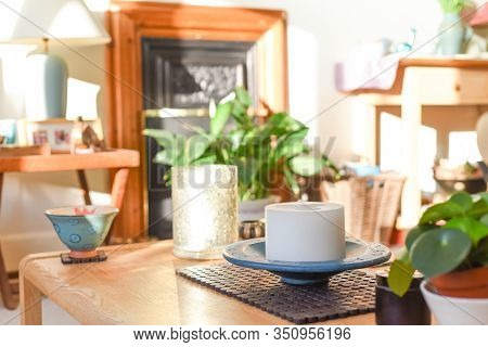 Stylish Home Interior In Natural Daylight From Window With Candle Ornament On Coffee Table