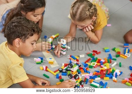 Kids Playing Block Toys In Playroom At Nursery. Four Children Playing Constructor While Laying On Th