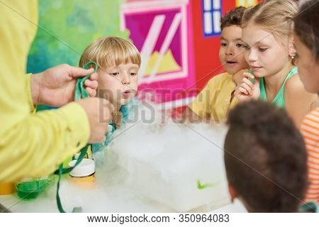 Experiment With Dry Ice For Kids. Birthday Party For Kids Steaming Liquid. Concept Of Kids Leisure.