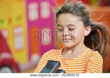 Little Girl With Closed Eyes Having Fun In Playroom. Cute Kid Playing In Entertainment Center.