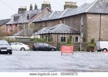 Road Flood Closed Sign Under Deep Water During Bad Extreme Heavy Rain Storm Weather In Uk